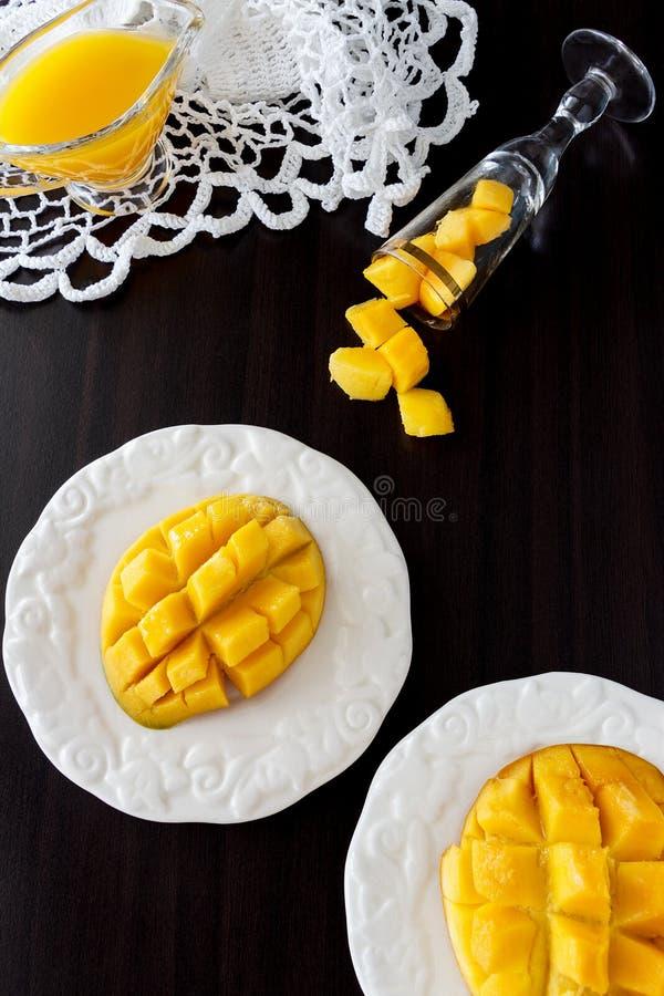 Cubetti di frutta del mango e purè del succo del mango su fondo di legno scuro immagini stock libere da diritti
