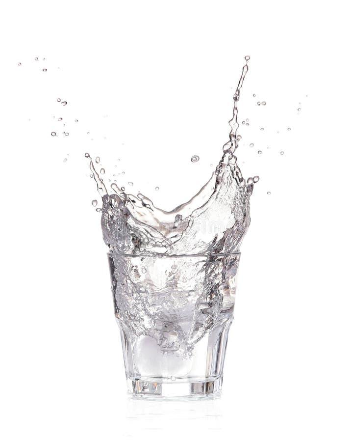 Cubetti di ghiaccio che spruzzano nel bicchiere d'acqua, isolato fotografie stock