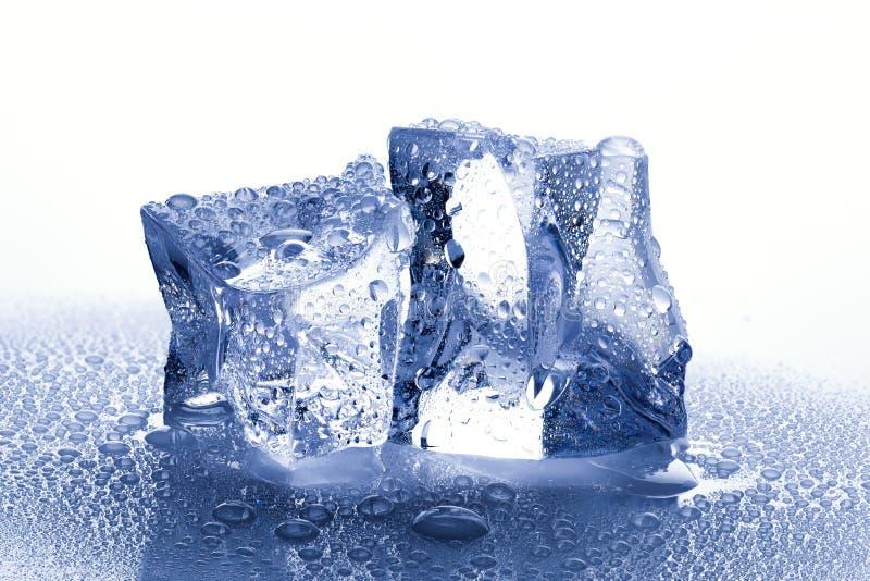 Cubetti di ghiaccio con i waterdrops su fondo bagnato bianco immagini stock libere da diritti