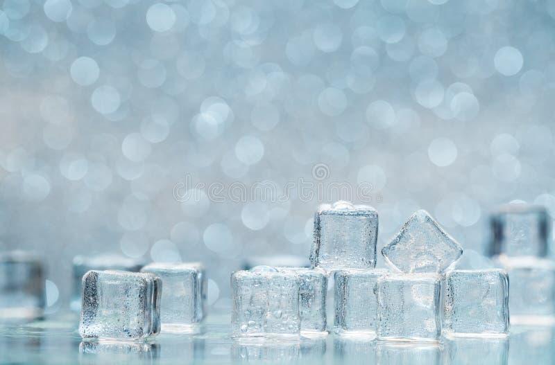 Cubetti di ghiaccio di fusione freddi con le gocce di acqua su fondo blured fotografia stock libera da diritti