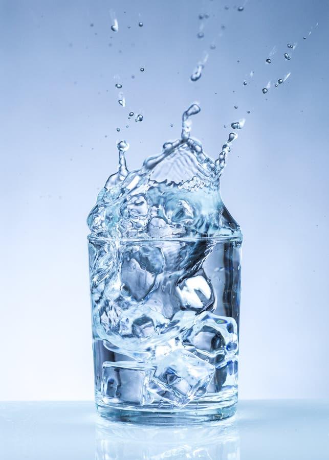 Cubetto di ghiaccio in un bicchiere d'acqua fotografia stock
