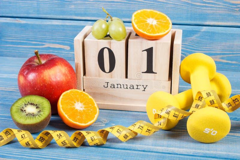 Cubez le calendrier avec la date du 1er janvier, des fruits, des haltères et du ruban métrique, nouvelles années de résolutions photographie stock libre de droits