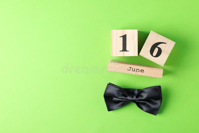 Cubi data di calendario 16 giugno e cravatta a farfalla di legno sul fondo di colore immagini stock