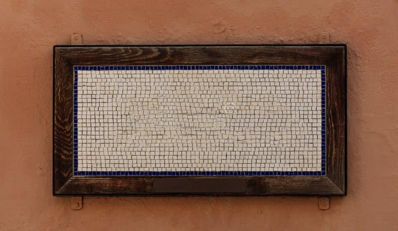 Cubi del mosaico nel telaio di legno con spazio per testo Fondo marrone caldo, fine sulla vista fotografia stock