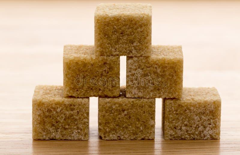 Cubi dello zucchero di canna di Brown su fondo di legno Macro fotografie stock