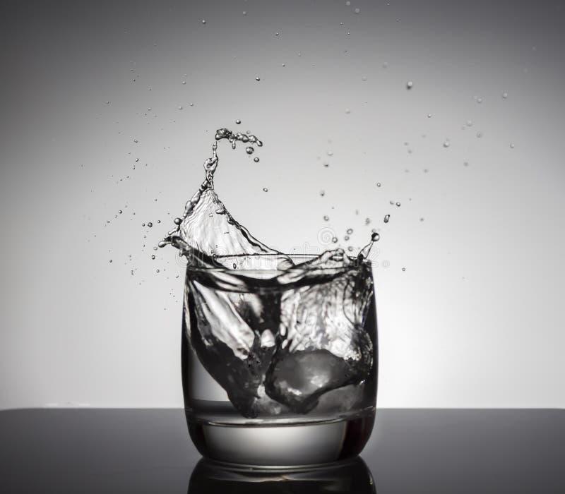 Cubi di ghiaccio che spruzzano nel vetro di acqua immagini stock libere da diritti