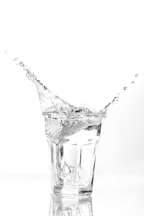 Cubi di ghiaccio che spruzzano nel vetro di acqua immagini stock