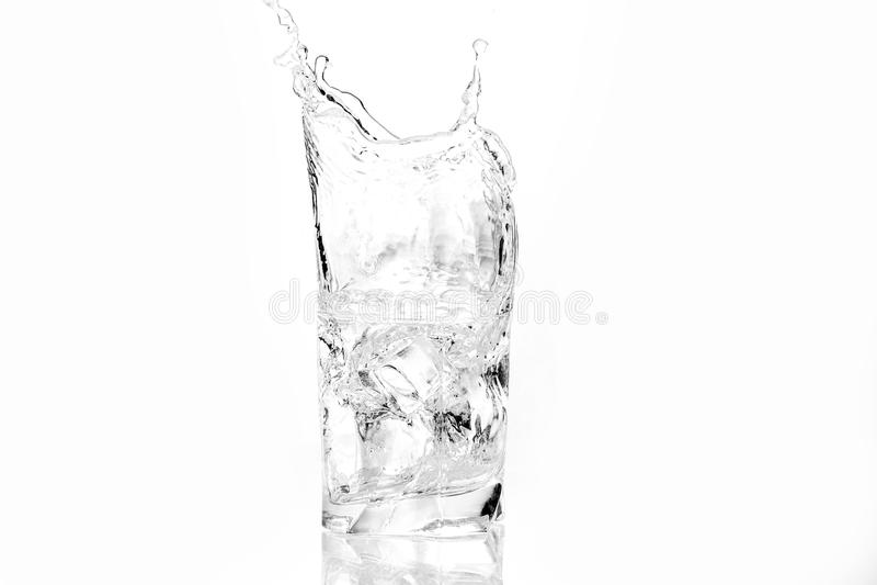 Cubi di ghiaccio che spruzzano nel vetro di acqua fotografie stock