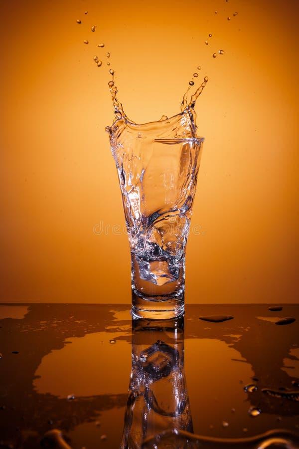 Cubi di ghiaccio che spruzzano nel vetro di acqua fotografie stock libere da diritti