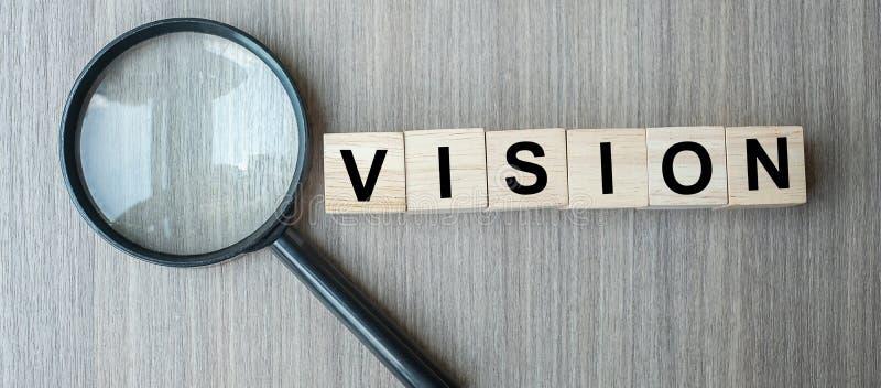 Cubi e lente d'ingrandimento di legno del testo di visione sul fondo di legno della tavola SEO, idea, strategia, analisi, scopi e immagine stock