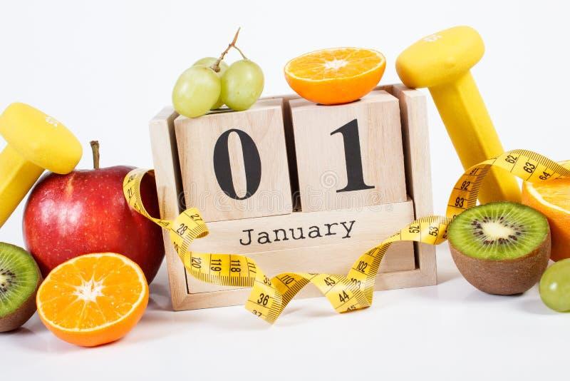 Cubi il calendario con data il 1° gennaio, i frutti, le teste di legno e la misura di nastro, nuovi anni di risoluzioni fotografie stock