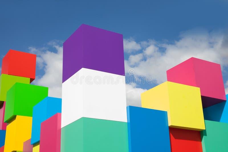 Cubi variopinti contro le nuvole di bianco del cielo blu Blocchi colorati gialli, rossi, verdi, rosa Pantone colora il concetto immagine stock