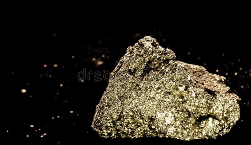 Cubic pyrite crystal stone, cat gold, in front of a black background with blurred fragments at a distance. Cubic pyrite crystal stone, cat gold, in front of a royalty free stock photography