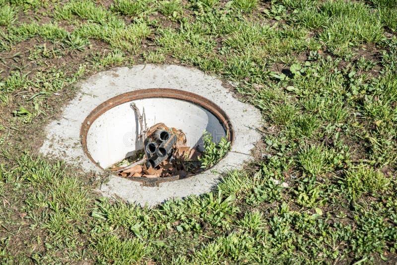 Cubierta abierta peligrosa del agujero de la boca, peligro para la gente que camina en la hierba en el parque en la ciudad fotografía de archivo libre de regalías