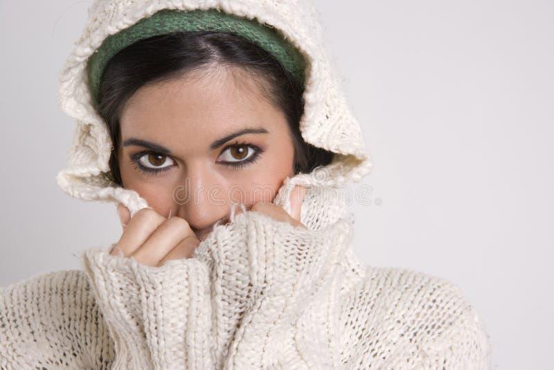 Cubierta atractiva de la mujer media su cara con el suéter fotografía de archivo libre de regalías