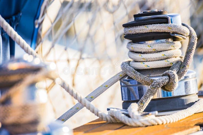 Cubierta de barco del yate de la navegación con el primer de la cuerda náutica amarrada en el torno foto de archivo