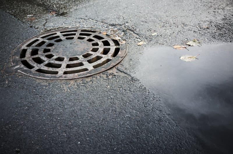 Cubierta de boca redonda de la alcantarilla en asfalto urbano imagen de archivo