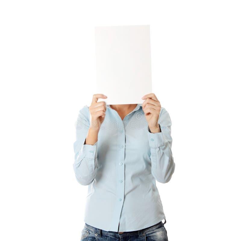 Cubierta de la muchacha su cara con la tarjeta en blanco fotos de archivo libres de regalías