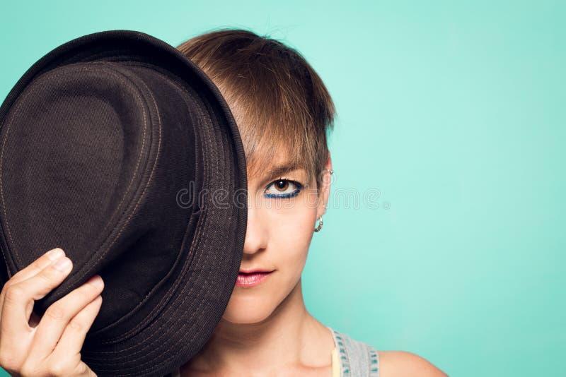 Cubierta de la mujer media su cara con un sombrero fotos de archivo