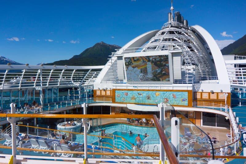 Cubierta de la piscina del barco de cruceros con las montañas de Alaska imagen de archivo libre de regalías