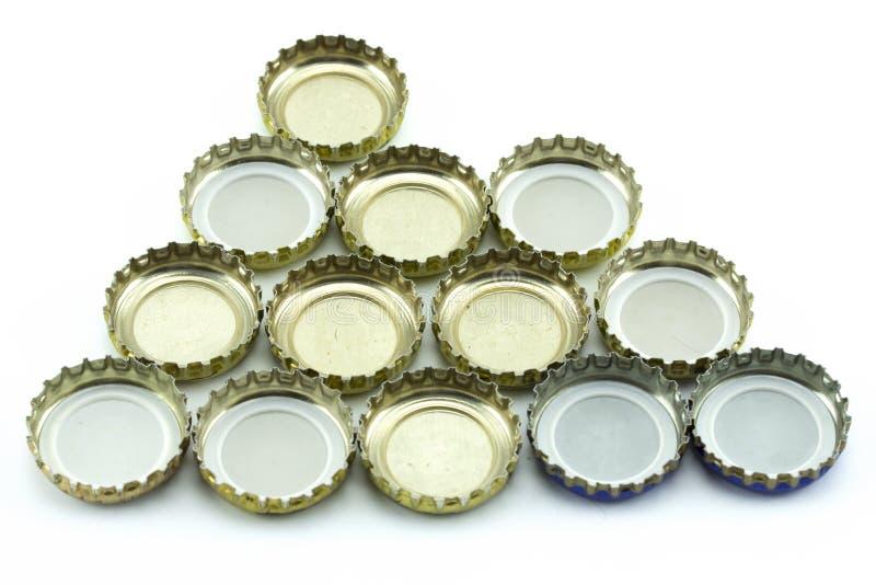 Cubierta del metal de las botellas de cristal Casquillos decorativos de la cerveza en el fondo blanco imágenes de archivo libres de regalías