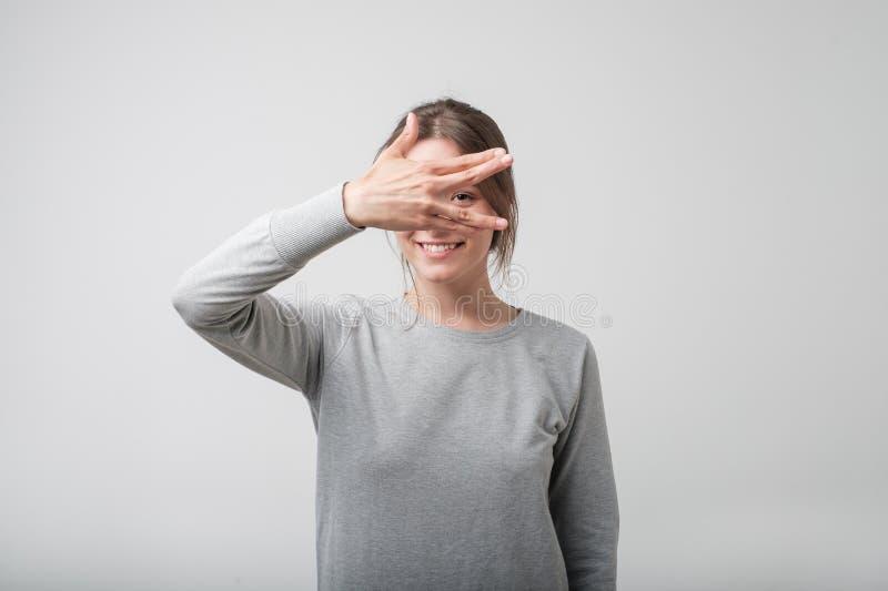 Cubierta femenina europea feliz joven su cara usando las manos imagen de archivo