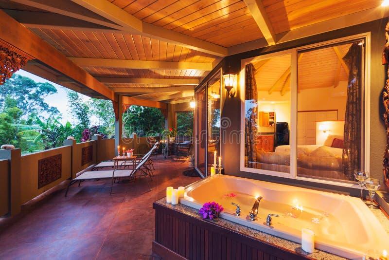 Cubierta romántica en hogar tropical con la bañera y las velas foto de archivo