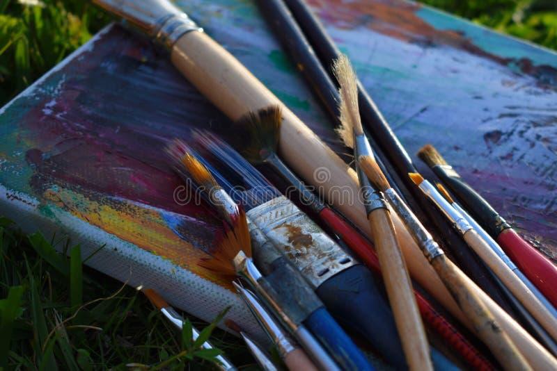 Cubierto con las pinturas de la paleta de los dibujos Cepillos sucios del arte para pintar el dibujo por las pinturas de aceite foto de archivo libre de regalías