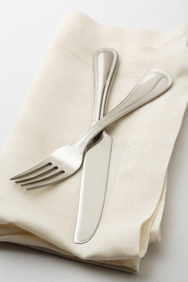 Cubierto de cena fino simple, casual con la bifurcación de alta calidad de los cubiertos y cuchillo en la servilleta de lino blan foto de archivo
