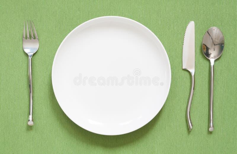 Cubierto de la cena una placa blanca con la bifurcación y la cuchara de plata imágenes de archivo libres de regalías