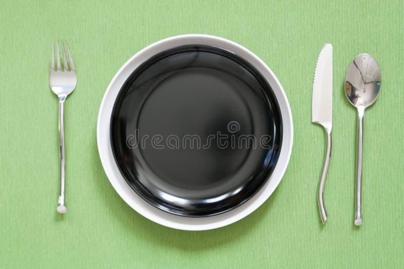 cubierto de la cena una placa blanca con la bifurcación y la cuchara de plata GR fotos de archivo