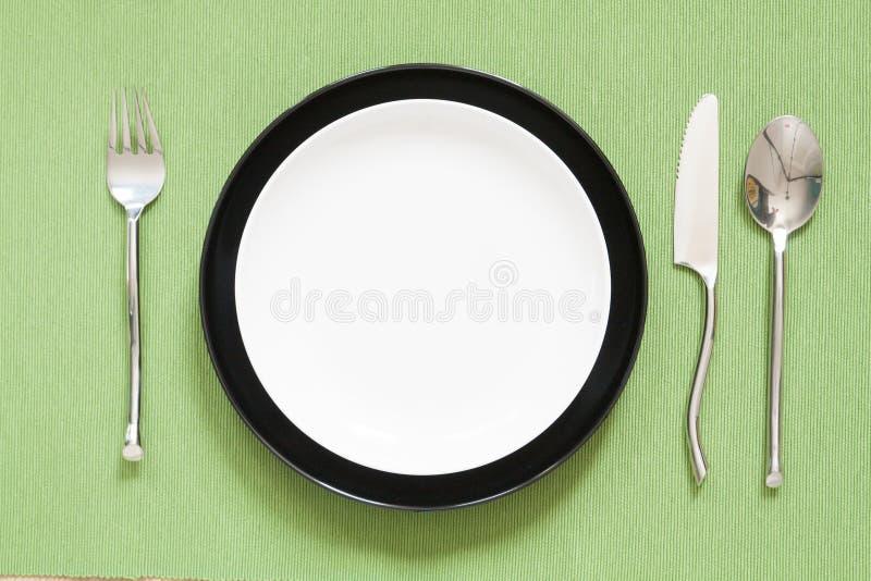 cubierto de la cena una placa blanca con la bifurcación y la cuchara de plata GR fotografía de archivo libre de regalías