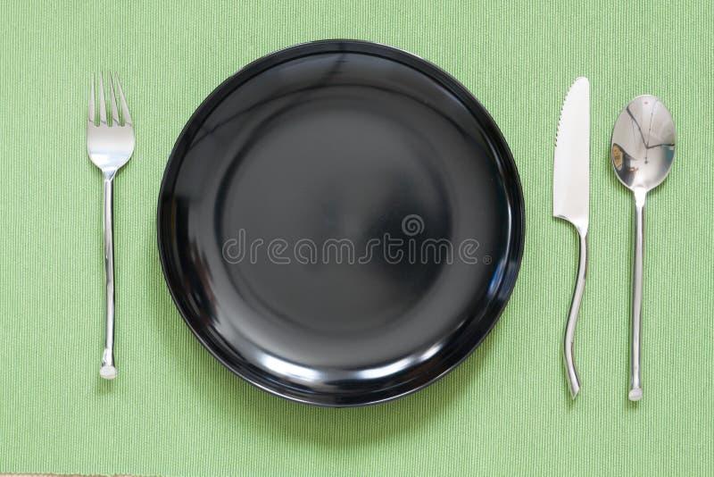 cubierto de la cena una placa negra con la bifurcación y la cuchara de plata GR imagen de archivo libre de regalías