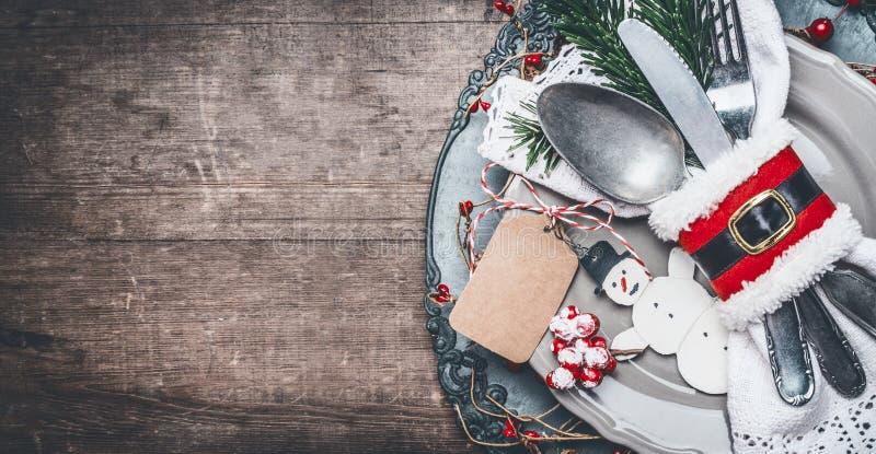 Cubierto de la tabla de cena de la Navidad del vintage con la placa, los cubiertos, las ramas del abeto, la mofa en blanco de la  imagenes de archivo