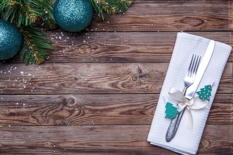Cubierto de la tabla de la Navidad con la bifurcación y cuchillo, cinta y arco adornado con los juguetes del abeto, servilleta bl fotos de archivo libres de regalías
