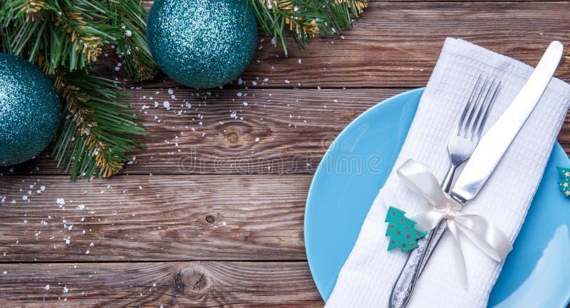 Cubierto de la tabla de la Navidad con la placa azul, bifurcación y cuchillo, cinta adornada y arco con el juguete del abeto, ser fotos de archivo libres de regalías