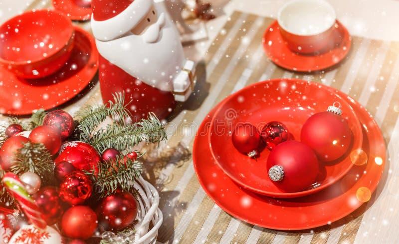 Cubierto de la tabla de la Navidad con la guirnalda de la Navidad, ramas del abeto, conos, decoraciones con el bokeh imagen de archivo