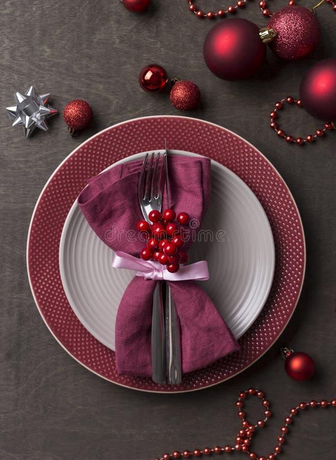 Cubierto de la tabla de la Navidad con las placas grises y rojas vacías, con las decoraciones festivas en el fondo de madera imagenes de archivo
