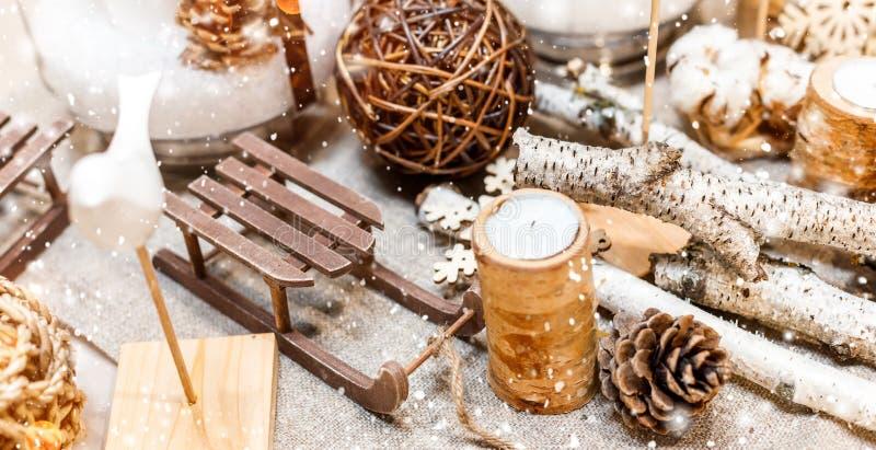 Cubierto de la tabla de la Navidad con los conos del pino de la Navidad, decoraciones de madera, bokeh, copos de nieve imagen de archivo