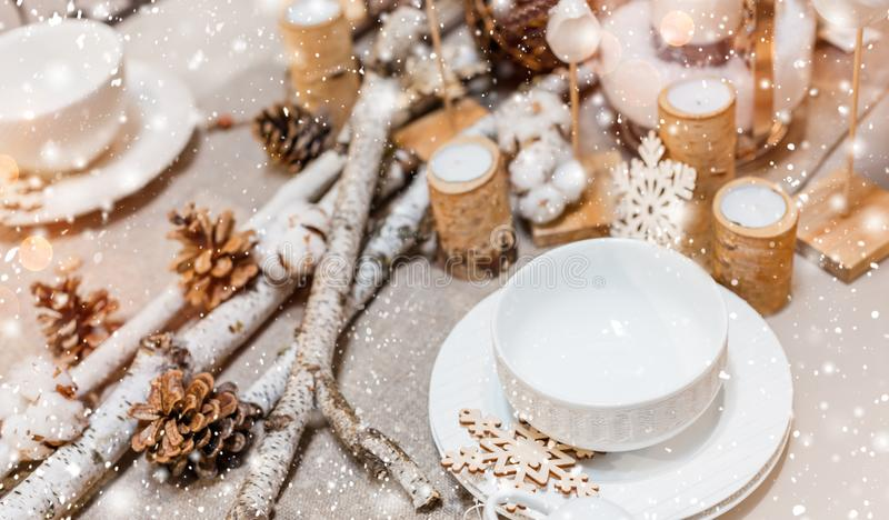Cubierto de la tabla de la Navidad con los conos del pino de la Navidad, decoraciones de madera, bokeh, copos de nieve foto de archivo libre de regalías