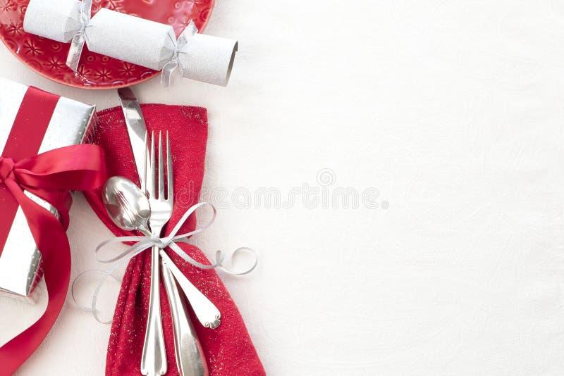 Cubierto de la tabla de la Navidad en rojo, blanco y de plata con los cubiertos, un regalo, y la galleta del partido en el fondo  foto de archivo