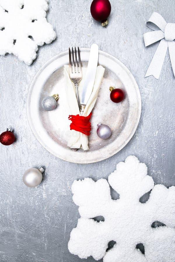 Cubierto de la tabla de la Navidad Fondo de los días de fiesta Placa de plata, cuchillo y bifurcación con las decoraciones de la  fotografía de archivo