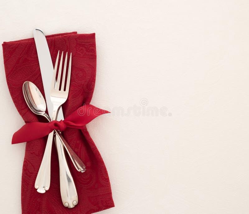 Cubierto de lujo de la Navidad o de la tabla de día de San Valentín con la servilleta, los cubiertos, y el arco rojos del paño en foto de archivo