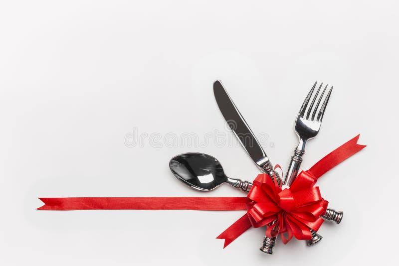 Cubierto festivo de la tabla con los cubiertos y el arco rojo y cinta en el fondo blanco, bandera Disposición para la cena del dí imagenes de archivo