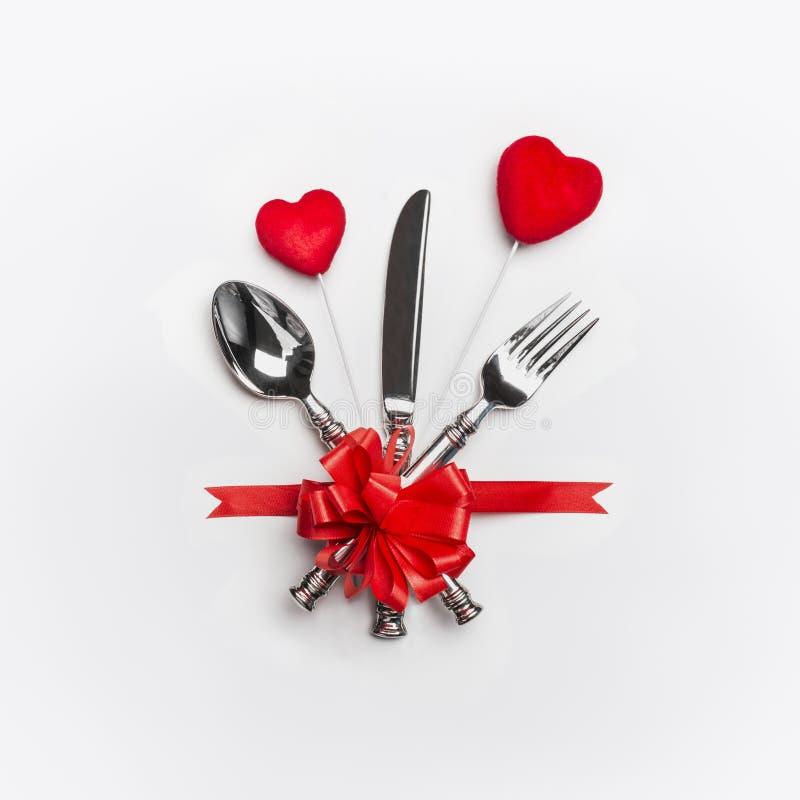 Cubierto festivo de la tabla con los cubiertos y el arco rojo y dos corazones en el fondo blanco Disposición para la cena del día foto de archivo