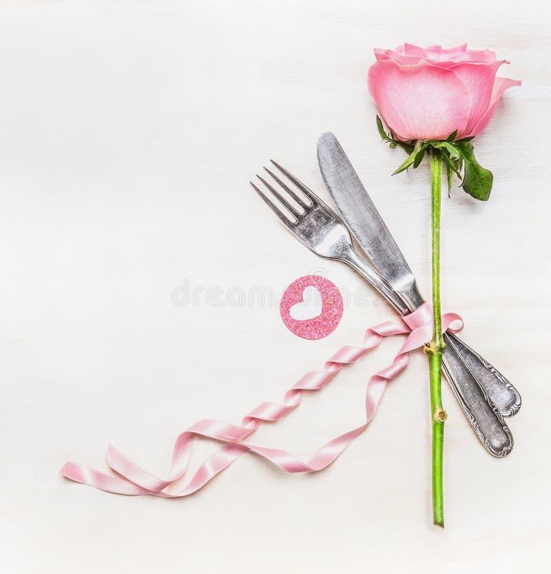 Cubierto romántico de la tabla de cena con la bifurcación, el cuchillo, la rosa del rosa y el corazón en el fondo de madera blanc foto de archivo