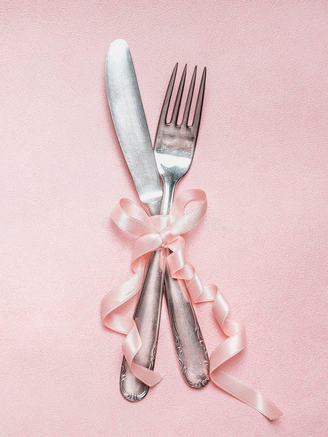 Cubierto romántico de la tabla de cena con la decoración de la cinta en el fondo pálido rosado, visión superior imágenes de archivo libres de regalías