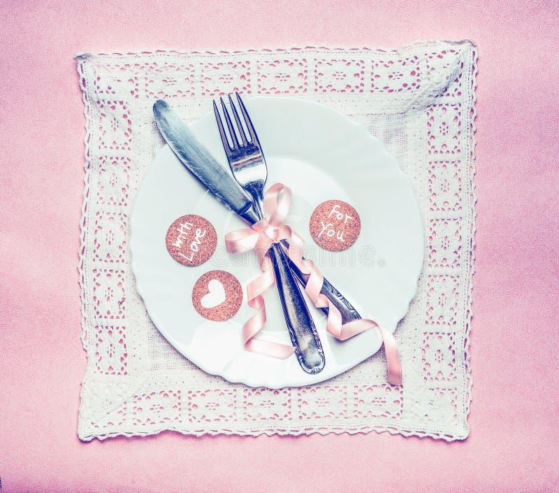 Cubierto romántico de la tabla de cena con las tarjetas de la decoración y del mensaje de la cinta en el tapetito y el fondo rosa fotografía de archivo