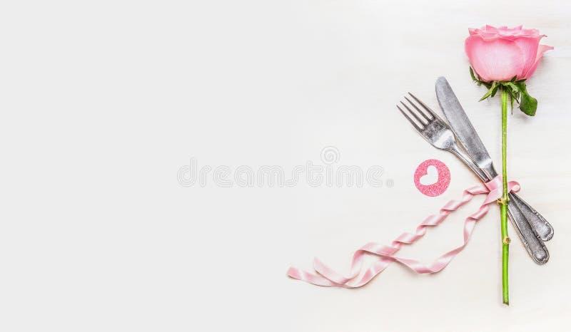 Cubierto romántico de la tabla de cena con símbolo color de rosa y del corazón en el fondo ligero, visión superior, bandera imagen de archivo