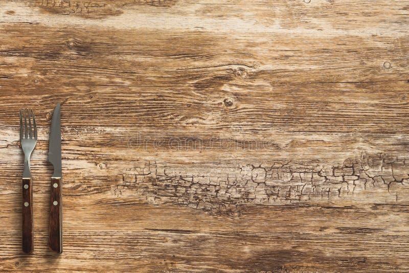 Cubiertos de la carne de la bifurcación y del cuchillo en la tabla de madera rústica imagen de archivo